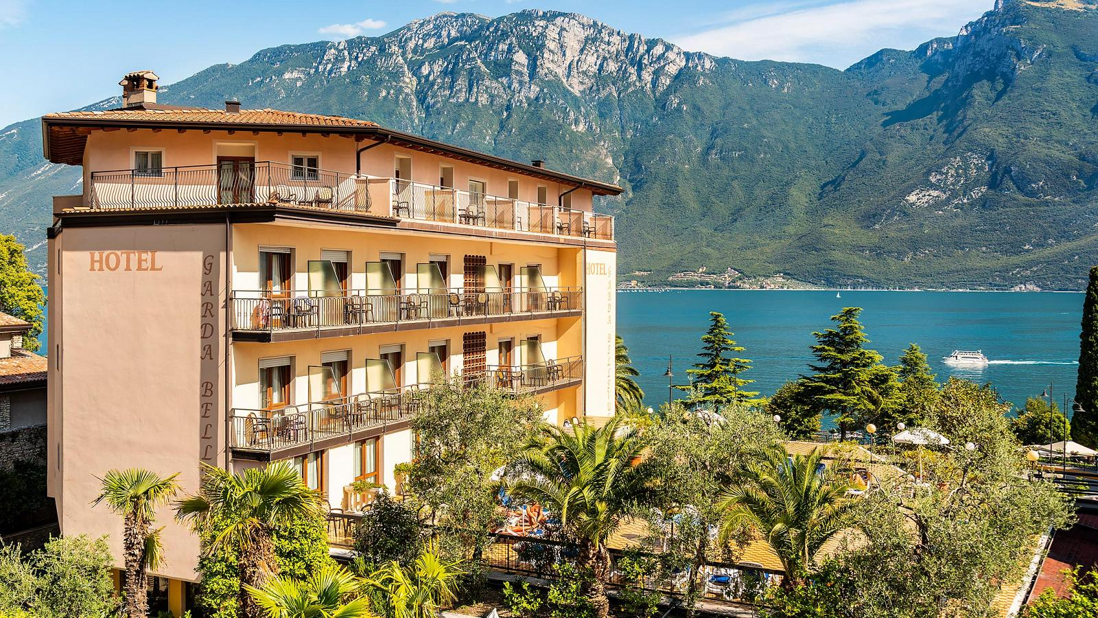 Panoramic view on Hotel Garda Bellevue with lake's shore and mountains behind